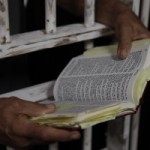 Inmate Prisoner Reading Holy Bible in Jail Prison Penitentiary Wide Pic